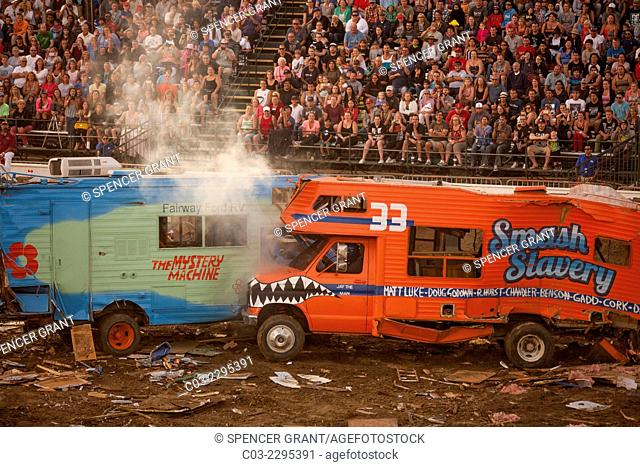 Steam rises from radiators as brightly painted motor homes crash together in a demolition derby at dusk at the Orange County Fair in Costa Mesa, CA
