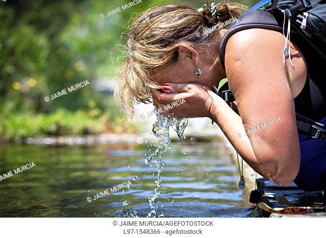 Woman splashing her face with water on the Camino de Santiago