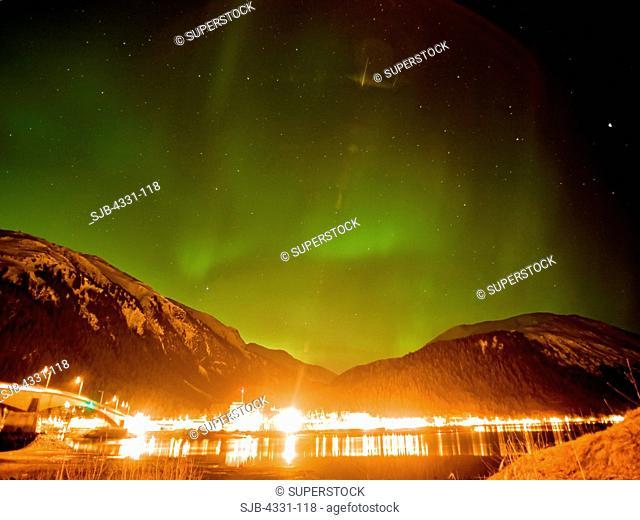 Above Juneau, Alaska, the northern lights aurora borealis blaze in the night sky, as seen from Douglas Island. The lights are seldom seen in southeast Alaska's...