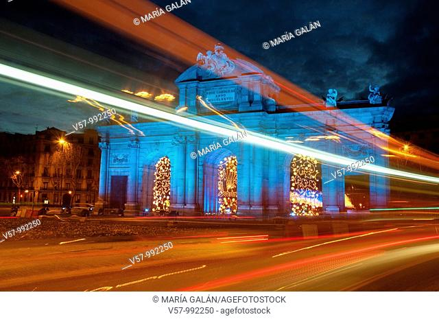 Puerta de Alcalá illuminated in blue and light trail, commemorating the Spanish presidency of European Union, night view. Madrid, Spain