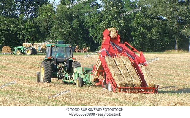 Farmer operating hay baler and accumulator
