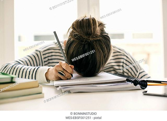 Woman writing on notepad resting her head on table