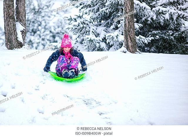 Girl tobogganing downhill