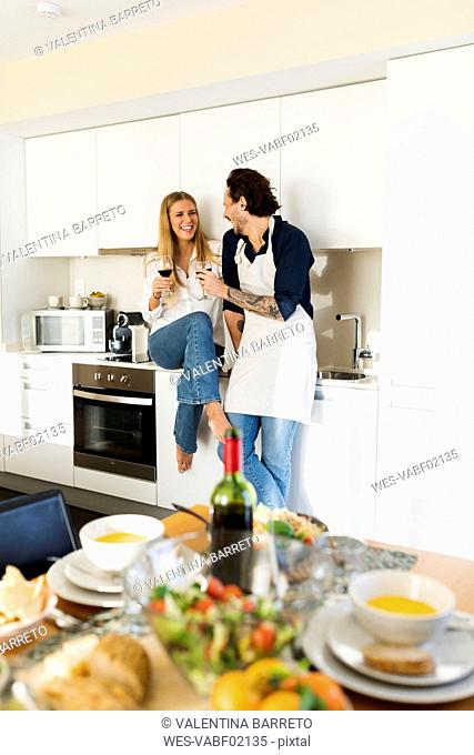 Couple preparing lunch for friends, drinking red wine, while waiting