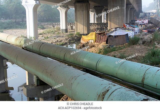 Makeshift shanty housing under freeway, Delhi, India