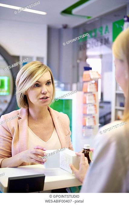 Woman discussing product with pharmacist in pharmacy