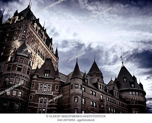 Low angle view of Fairmont Le Château Frontenac castle rooftops in twilight with dark stormy sky above, luxury grand hotel Chateau Frontenac