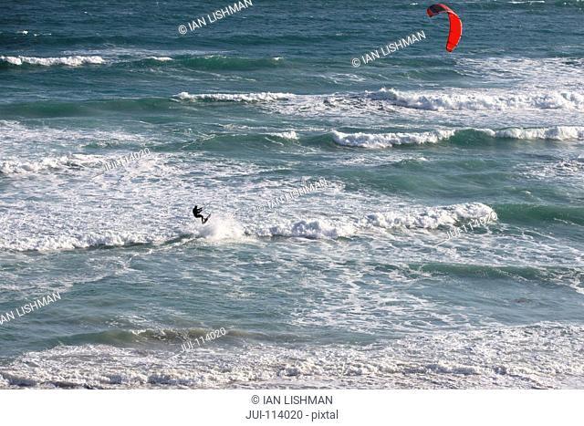 Aerial view kiteboarder kiteboarding on sunny windy ocean jumping waves