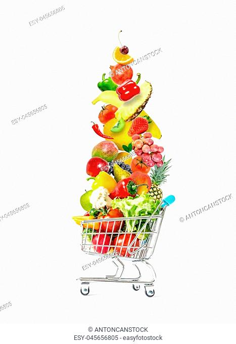 Fresh vegetables and fruits fly in a crowded shopping cart isolated on a white background. Mountain of fresh vegetables and fruits in a crowded shopping cart...