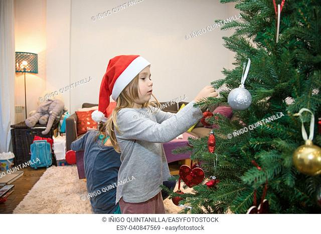four years blonde cute girl with red Santa Claus hat decorating a Christmas tree, with mother helping behind, at home