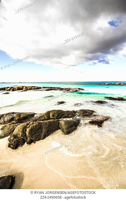 Postcard perfect ocean background with waves of turquoise blue rushing the shoreline. Bay of Fires in north eastern Tasmania Australia