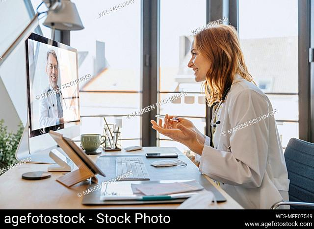 Healthcare worker talking to coworker on video call over computer while sitting at office