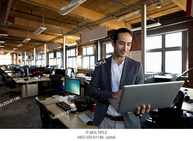 Businessman using laptop in open office