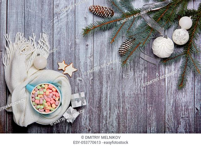 Mug of cocoa with marshmallow, woolen white scarf, gift boxes, fir tree branches and Christmas ornaments on grey wooden background