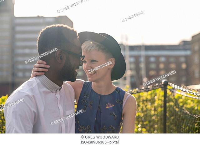 Young couple outdoors, hugging, smiling