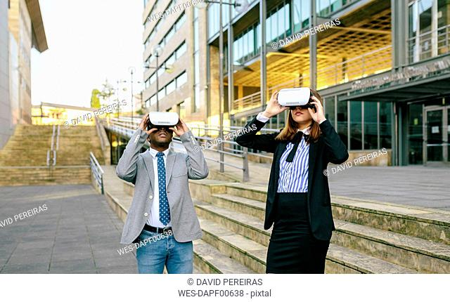 Young businessman and woman using VR goggles