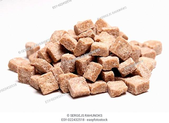 Heap of brown sugar cubes over a white background