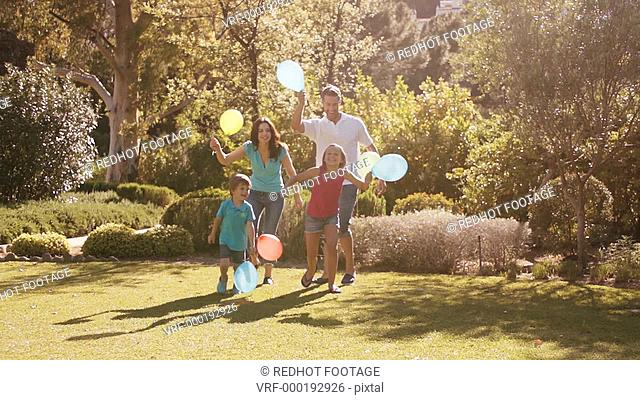 Slow motion of family in park running with balloons