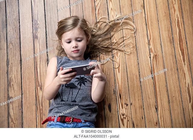 Little girl lying on floor using smartphone