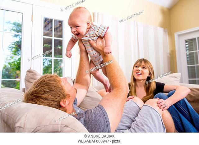 Parents with baby boy sitting on couch, smiling