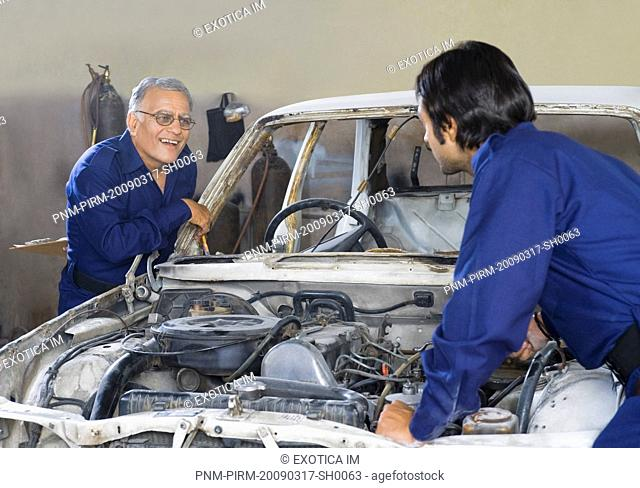 Auto mechanic with an apprentice repairing a car in a garage