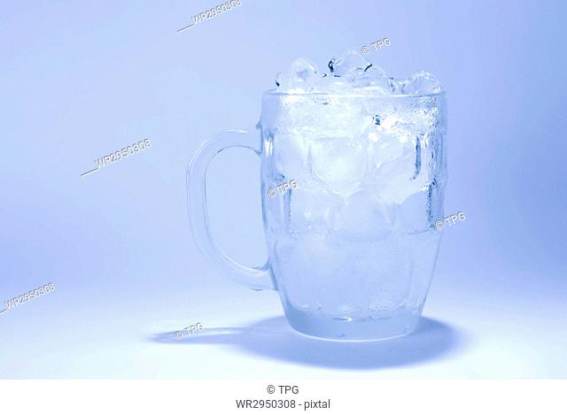 the glass full of ice cube with blue background