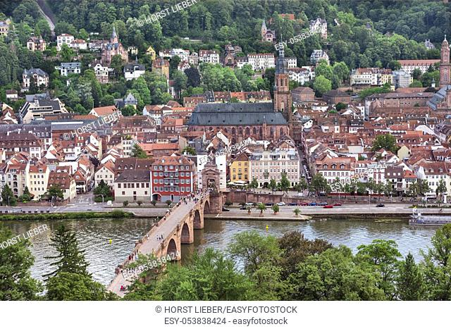 The historical old bridge gate with two towers in Heidelberg. In the background the Church of the Holy Spirit and the old town , Baden Wuerttemberg, Germany