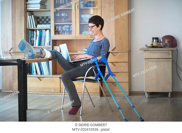 Woman resting her broken leg on table and using laptop on chair
