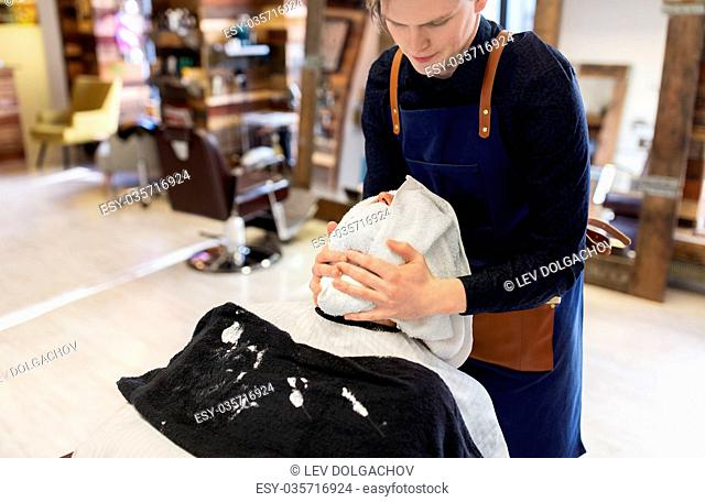 grooming, shaving and people concept - barber softening male clients face skin with hot towel at barbershop