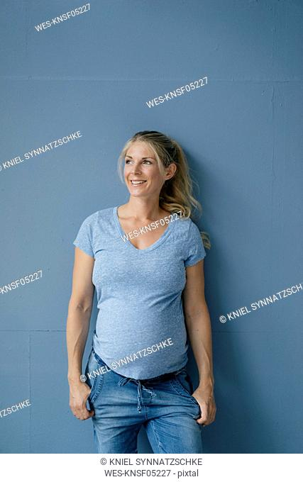 Portrait of smiling pregnant woman standing at blue wall