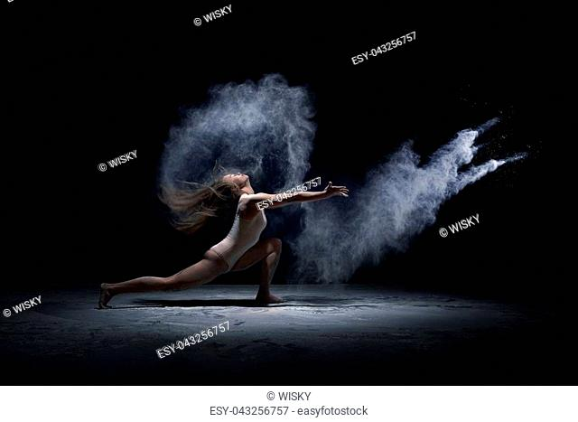 Young athletic dancer performing at dark studio in cloud of powder or dry paints