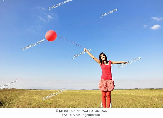 Happy young woman holding red balloon