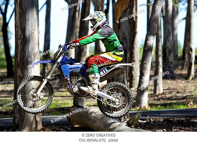 Young male motocross racer jumping on top of forest logs