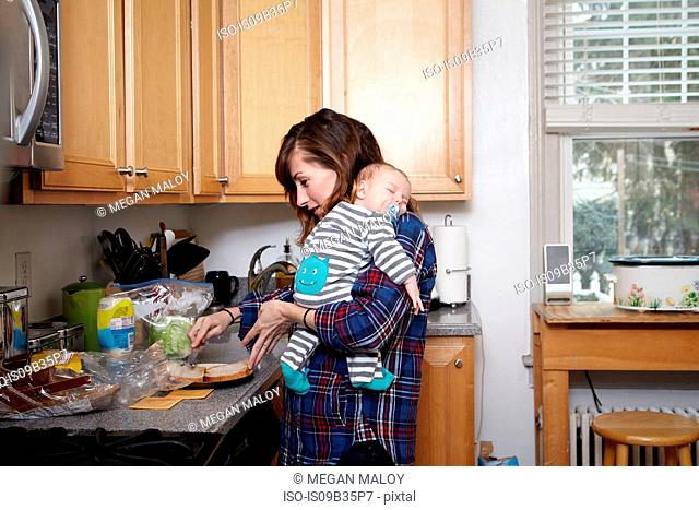 Mother holding sleeping baby boy and preparing sandwich