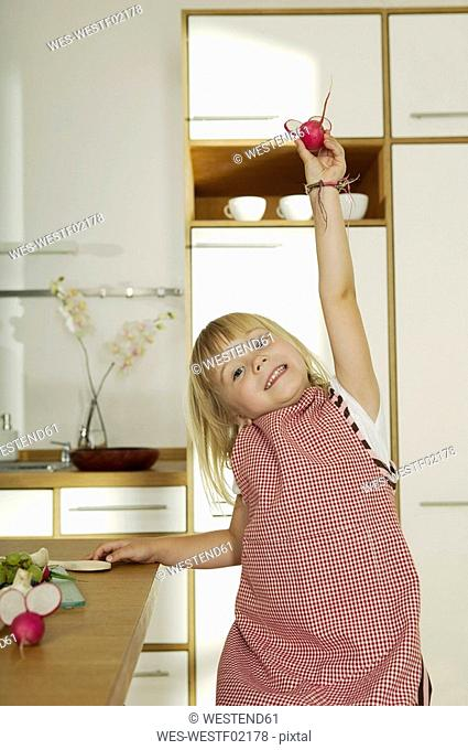 Girl 4-5 in kitchen, holding radish, close-up, portrait