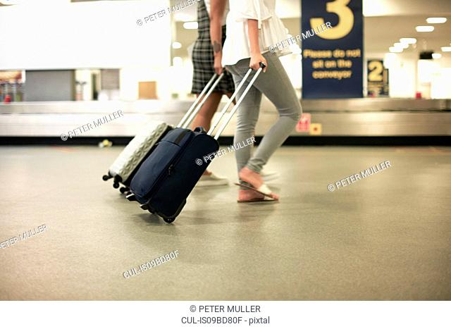 Friends with wheeled suitcases in airport