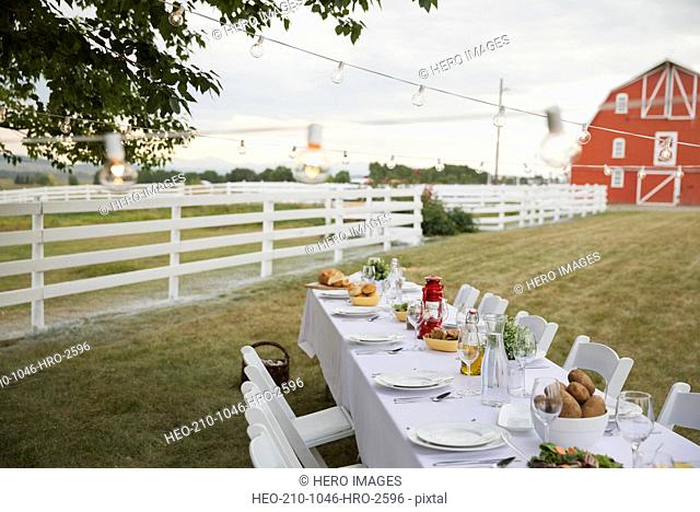 Empty dining table set up outdoors on farm