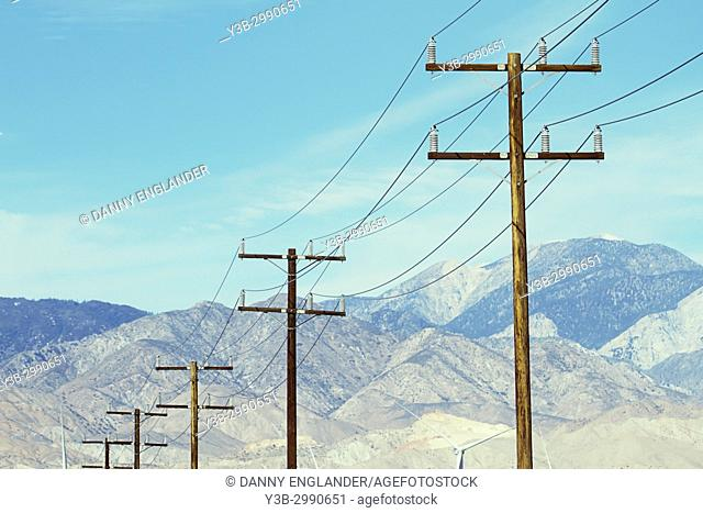 A row of telephone poles with rugged mountains in the background, Palm Springs, California