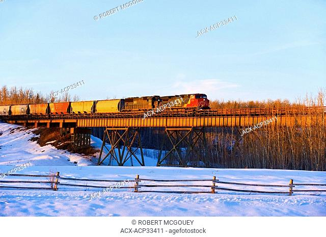 Canadian National freight train crossing a tressel lighted by a winters sunset in Alberta, Canada