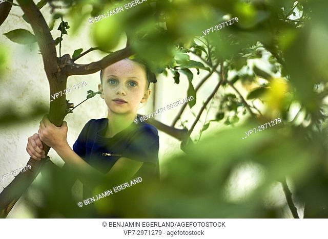 young girl in nature, between green leaves. Australian ethnicity