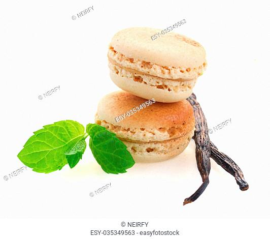vanilla macaroons with two vanilla sticks isolated on white background