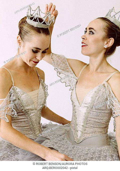 Two ballet dancers helping each other to dress