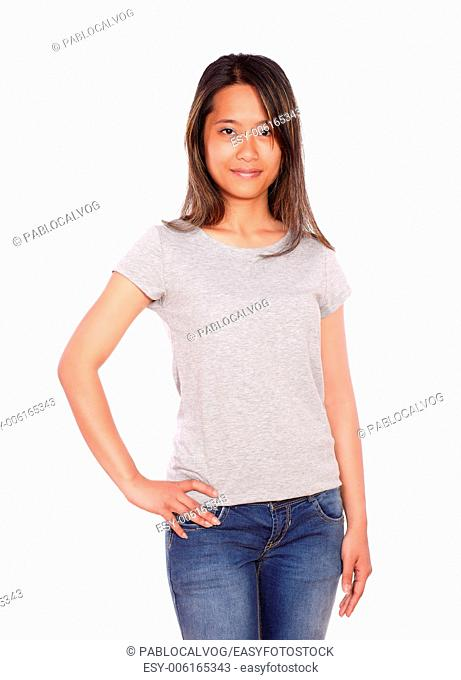 Portrait of an asiatic charming young woman looking at you on blue jeans against white background
