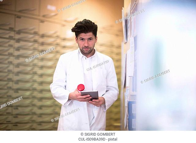 Portrait of young male pharmacist using digital tablet in pharmacy