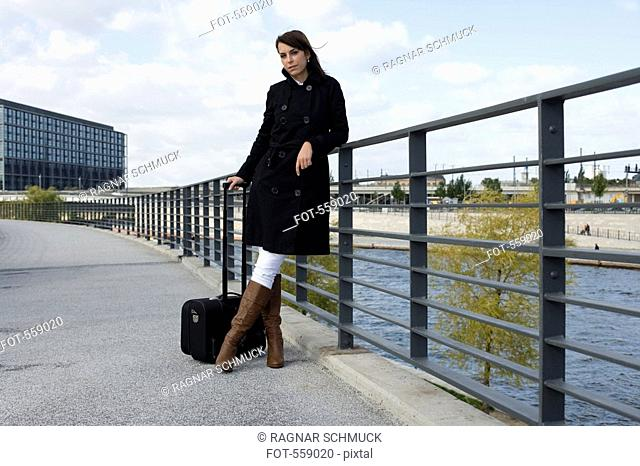 A woman standing on a bridge over a river with luggage