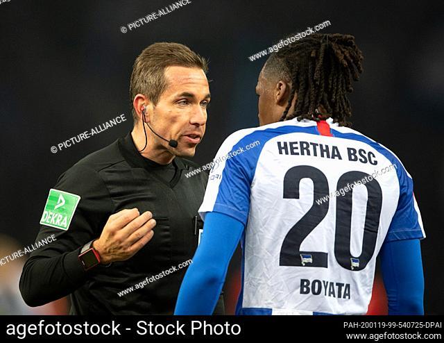 19 January 2020, Berlin: Football: Bundesliga, Hertha BSC - FC Bayern Munich, 18th matchday in the Olympic Stadium. Referee Tobias Stieler (l) cautions Dedryck...