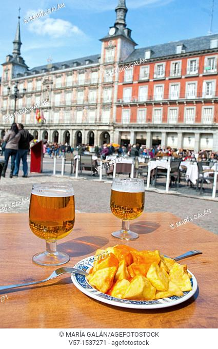 Spanish appetizer: patatas bravas and beer for two. Main Square, Madrid, Spain