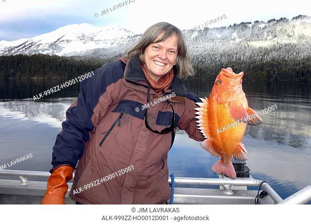 Woman holding a yelloweye rockfish red snapper in a bay near Homer, Kenai Peninsula, Southcentral Alaska
