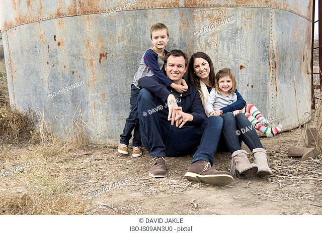 Portrait of parents and two children leaning against iron container