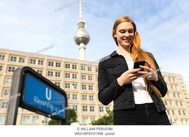 Portrait of smiling young woman at Alexanderplatz looking at cell phone, Berlin, Germany